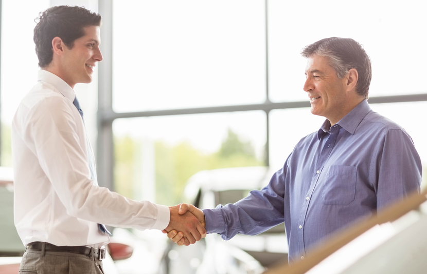 Businessman shaking a customer hand at new car showroom
